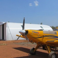 Lateral view of the Frisomat Omega+ airplane hangar with in the front the Embraer Ipanema agricultural plane.