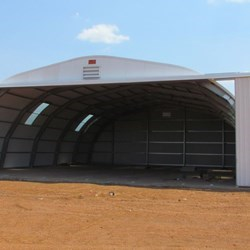 Frontal view of the Frisomat Omega+ with a span of 18m and a XXL door 15m wide and 5m high, the gate is open.