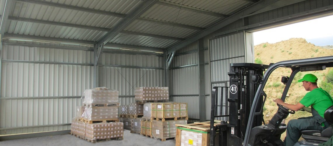 Interior view of a Delta hangar used as warehouse, showing a forklift stacking pallets